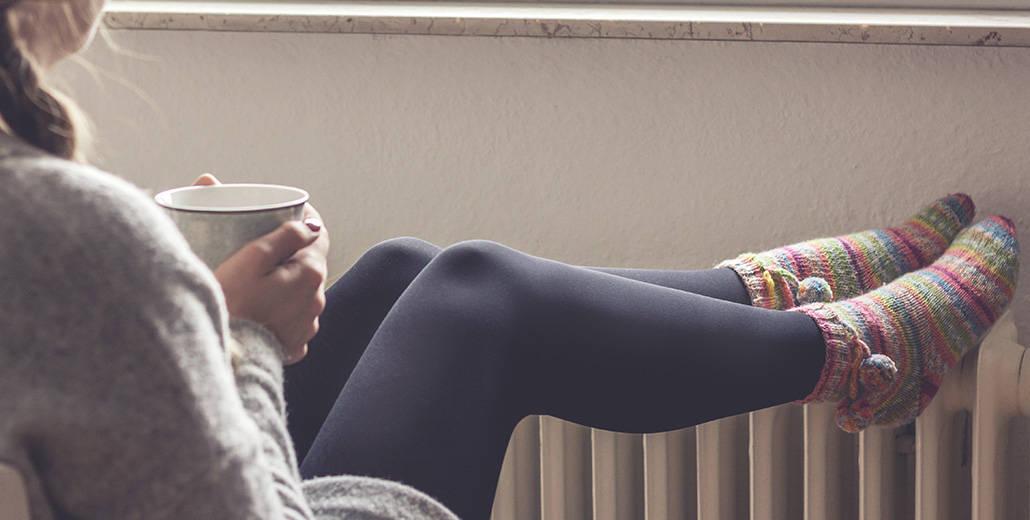Eine junge Frau wärmt sich die Füße am Heizkörper