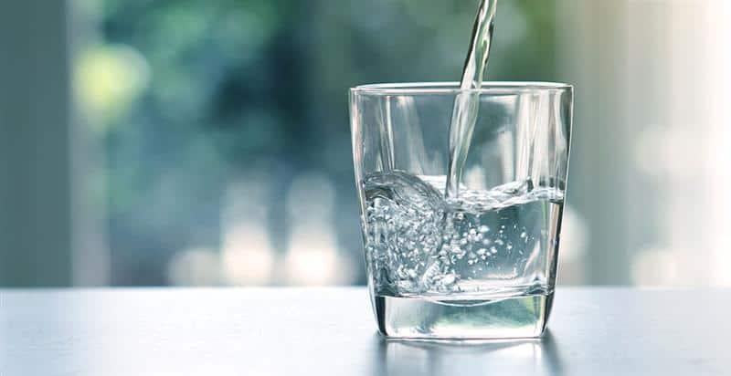 Pures, frisches Wasser wird in ein Glas gefüllt