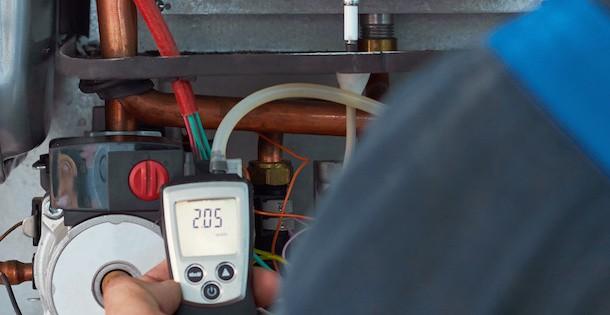 Klempner misst die Temperatur am Heizungsboiler
